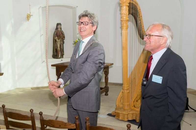 Burgemeester Bolsius luidt de klok. Voorzitter Verwers wacht af.